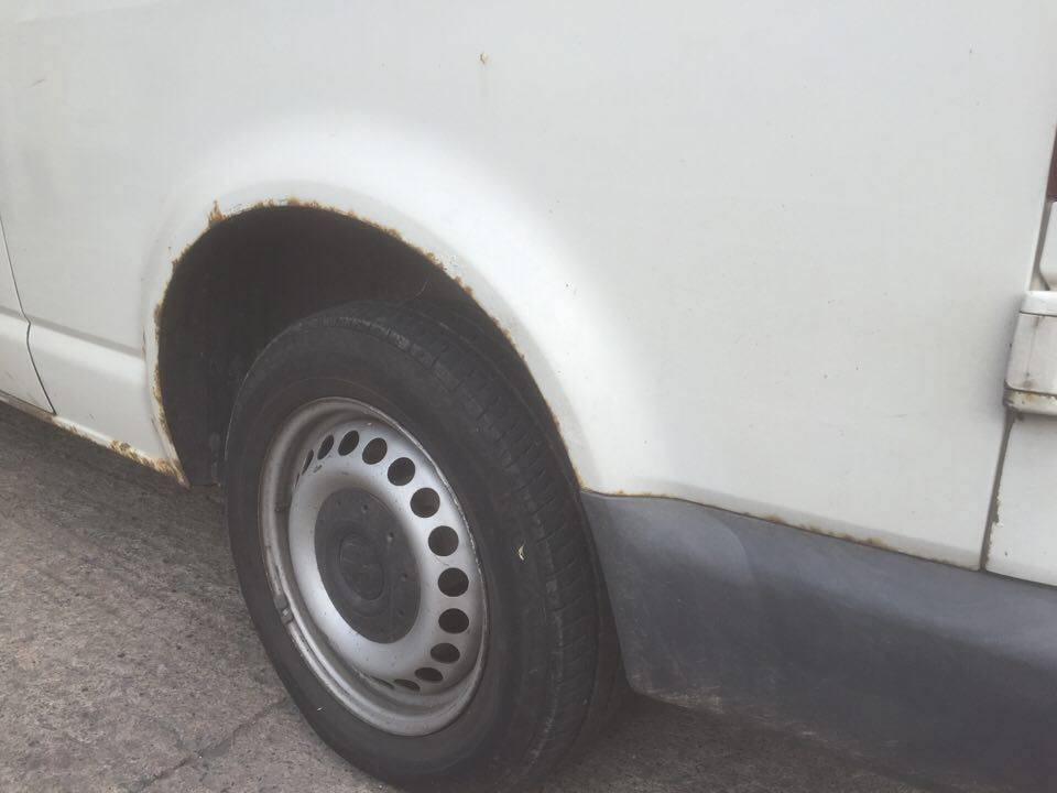 white camper van with rust in wheel arch