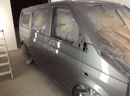 grey camper van being paint sprayed