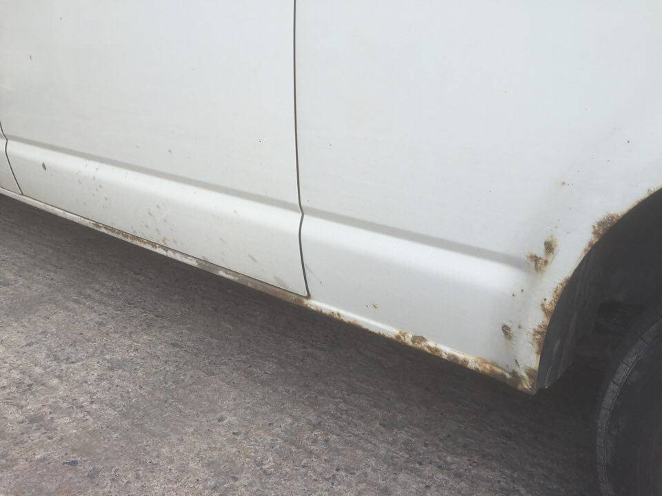 rust on exterior of white camper van